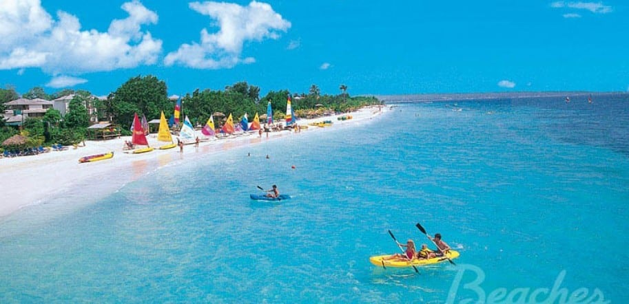 people in kajak, sail boats in the background, on the beach in front of Beaches Negril all inclusive family resort