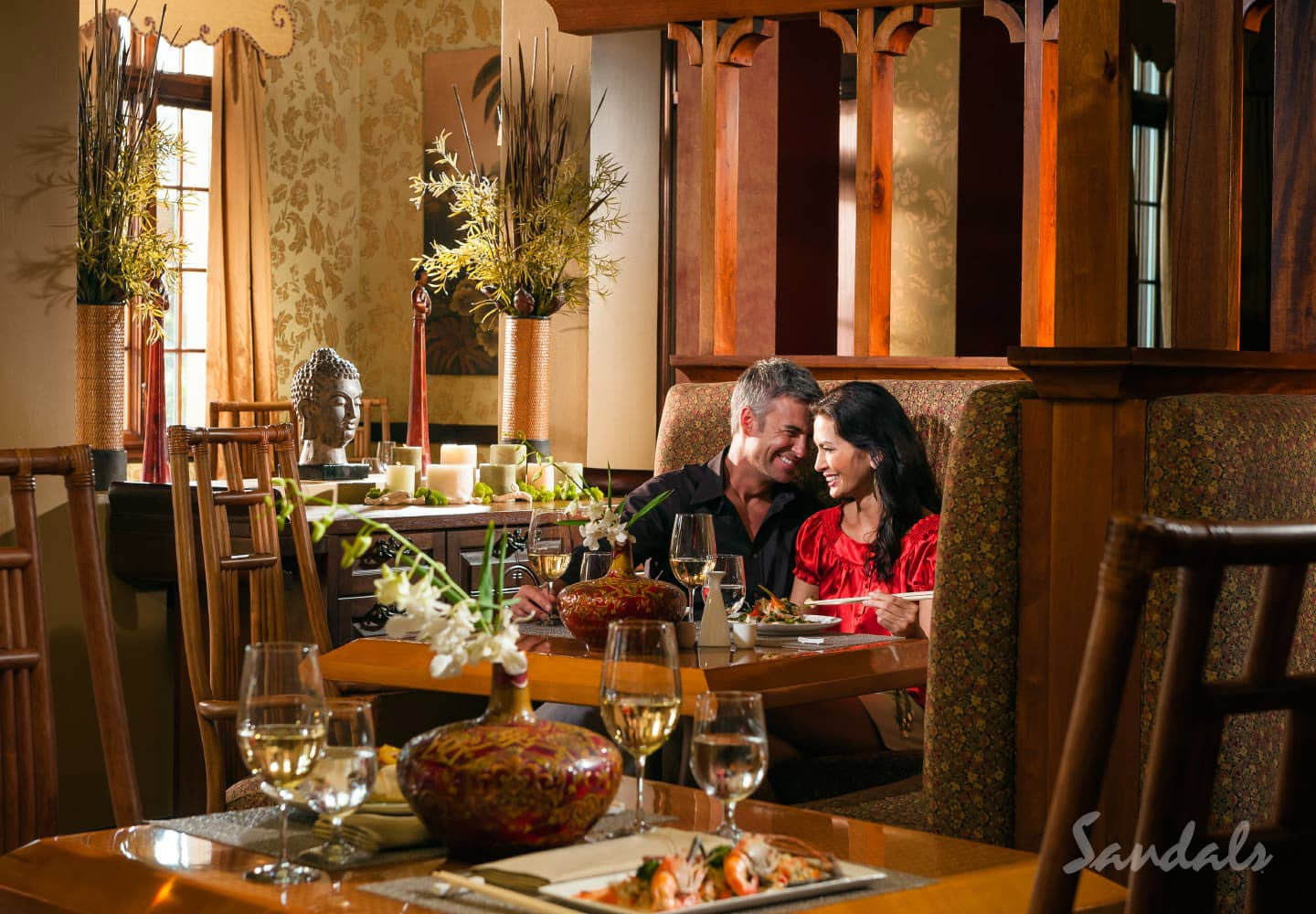 two people sitting in the wine restaurant Eleanor's at Sandals Whitehouse in Jamaica, enjoying entertainment at Sandals Whitehouse, resort can be booked through Southern Travel Agency Augusta, GA