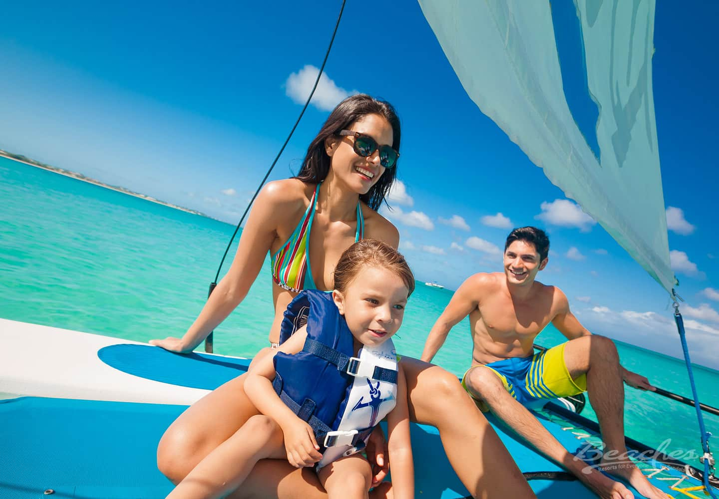 dad, mom, and daughter on a sail boat at the beaches turks and caicos resort, an all inclusive family resort