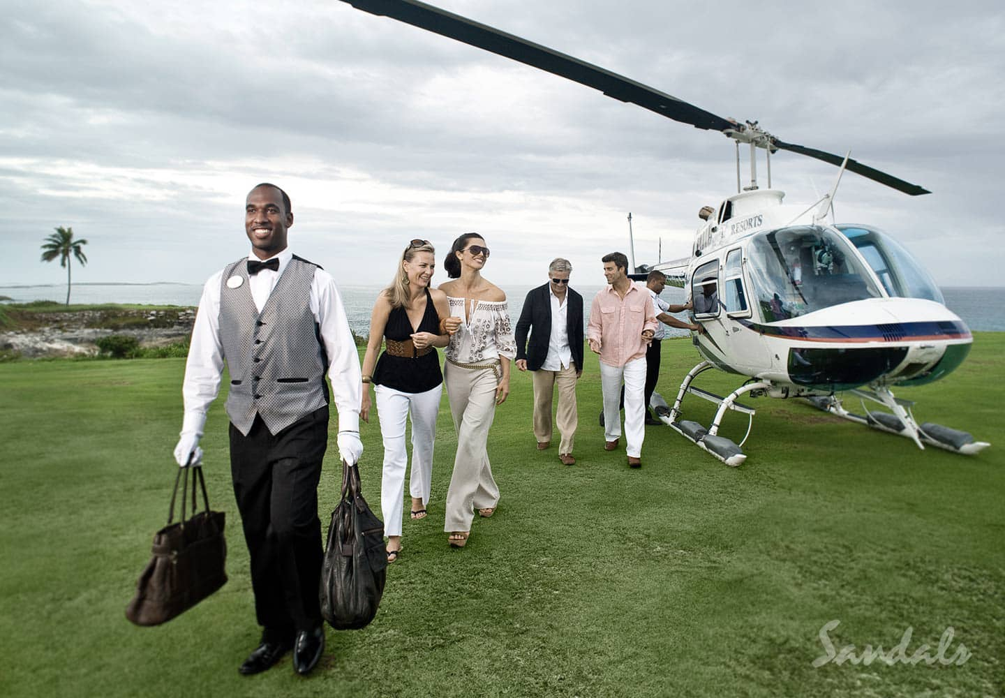 helicopter landing guests picked up from butler at the luxury Sandals Emerald Bay golf, spa, and tennis resort at the Great Exuma Bahamas, this adult only resort can be booked with Southern Travel Agency Augusta, GA