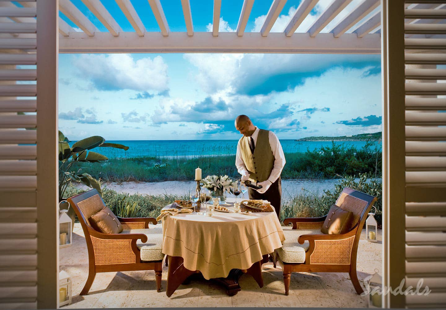 butler pouring in wine for a private dinner at the Sandals Emerald Bay Golf, Spa and Tennis Resort at the Great Exuma, Bahamas, vacation can be booked with Southern Travel Agency Augusta, GA