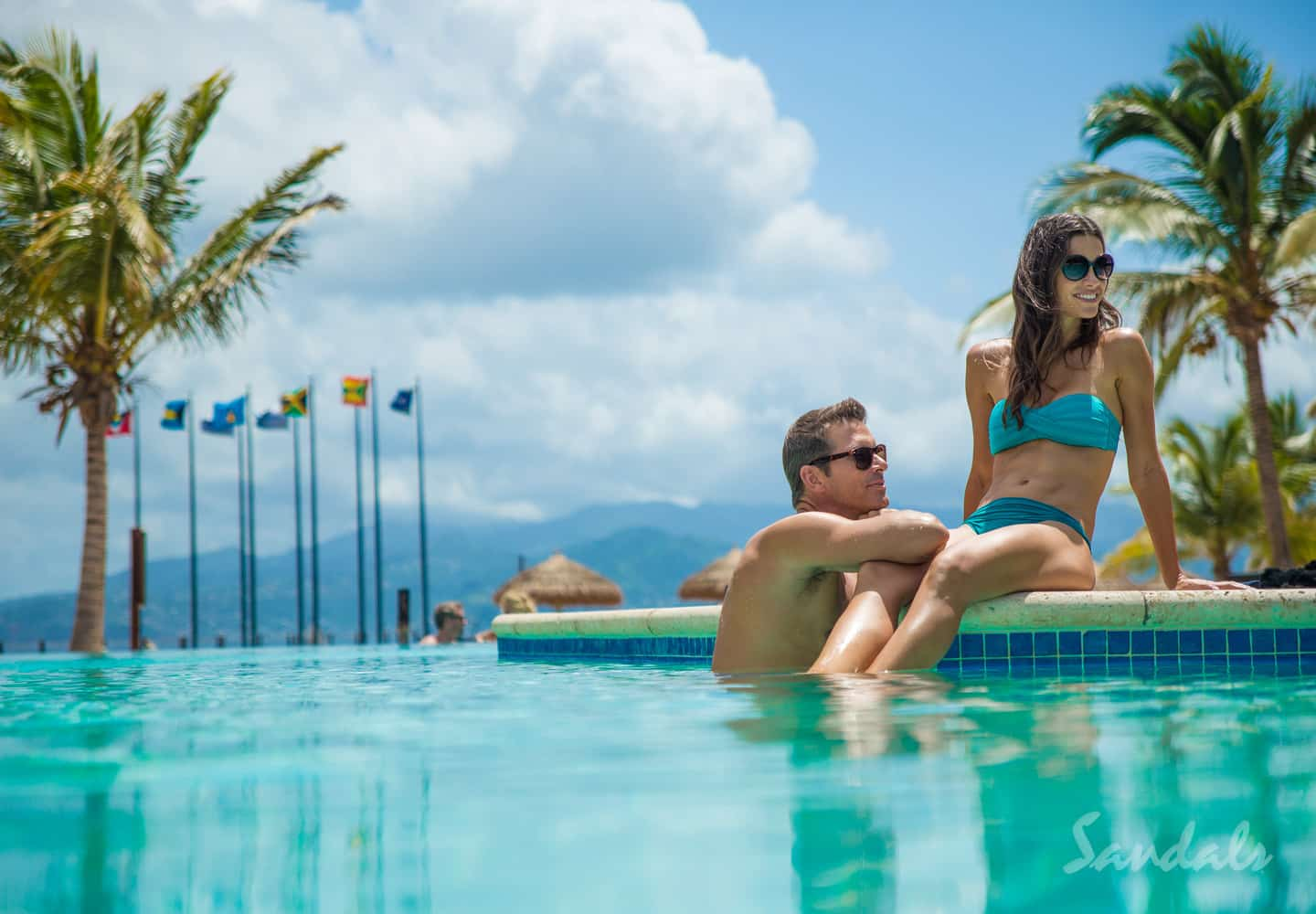 couple together in the pool, relaxing and having a good time at the Sandals LaSource Grenada luxury resort, adult only vacations can be booked with Southern Travel Agency Augusta, AG