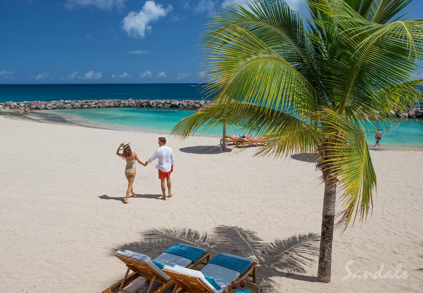 couple walking on the fine white powder sand beach at the Sandals LaSource Grenada luxury resort, adult only vacations can be booked with Southern Travel Agency Augusta, GA