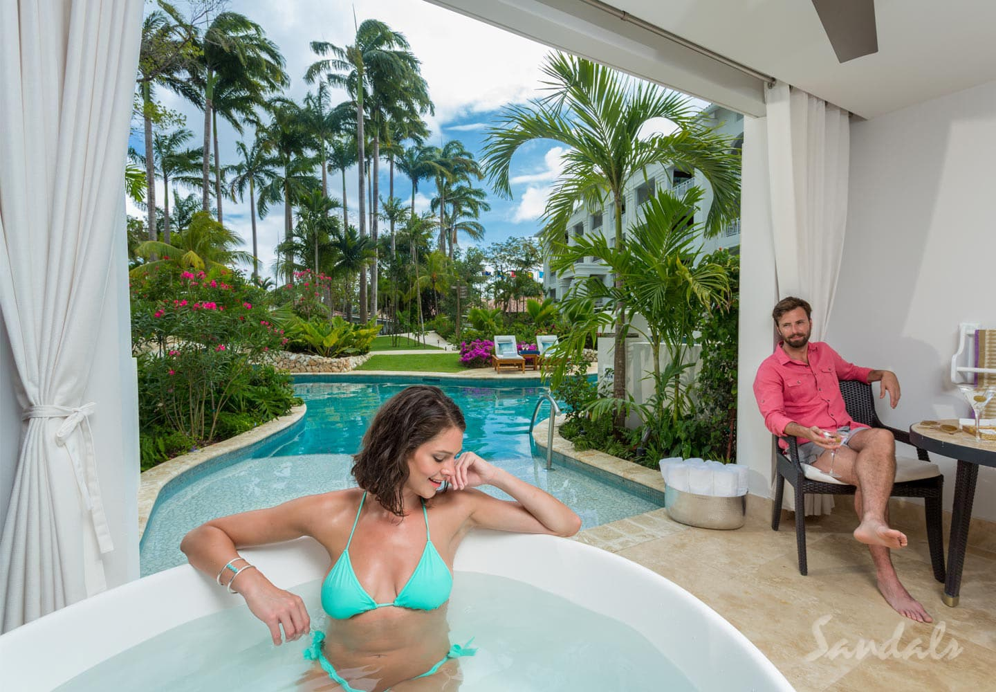 couple relaxing in their private room at Sandals Barbados resort all inclusive adult only, can be booked through Southern Travel Agency Augusta, GA