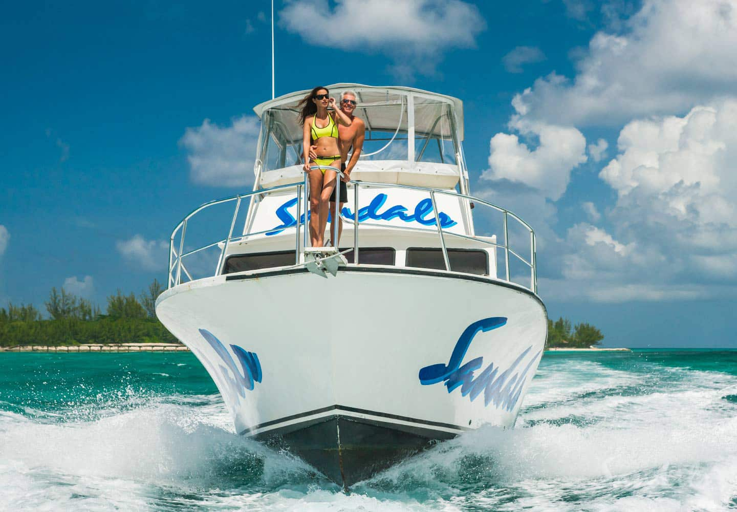 a couple on top of a yacht in the ocean at the Sandals Emerald Bay Golf, Spa & Tennis resort at the Great Exuma, Bahamas luxury resorts, all inclusive adults only vacation packages