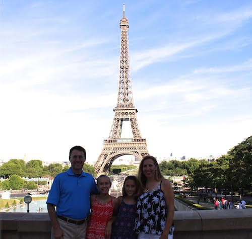 father, mother and two daughters in front of the Eiffel Tower in Paris, France
