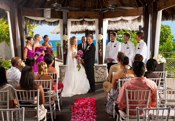 couple in front of friends getting married in a wedding chapel in a luxury resort, symbolizing the enjoyment of booking luxury all inclusive wedding vacation packages