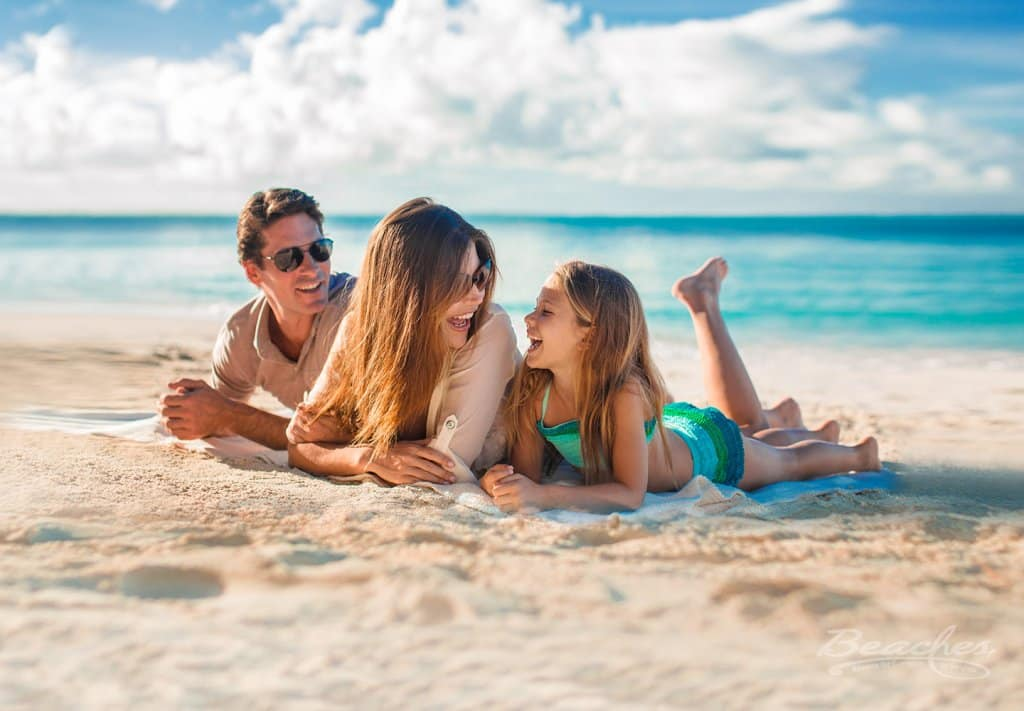 father, mother and child laying in the sand on a Sandals resort, laughing and having a good time on their all inclusive family vacations trip