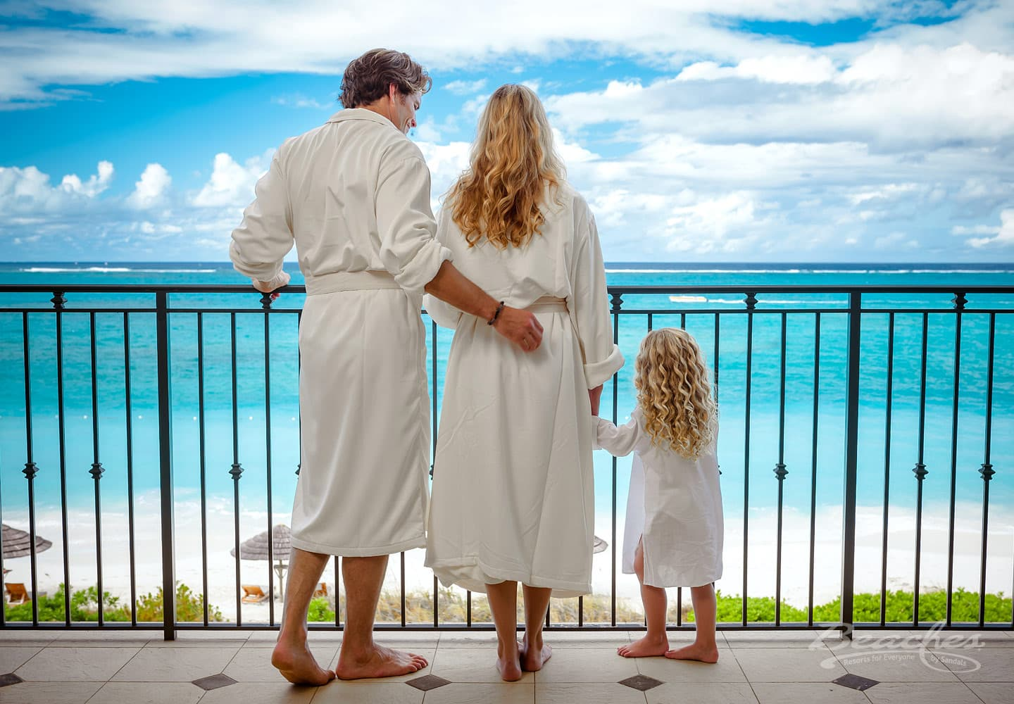 father, mother, and daughter in their white morning robe, standing on the balcony of their luxury resort room, part of their all inclusive family vacations package