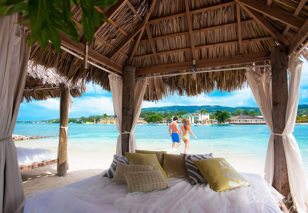 couple on the beach in front of their luxurious outside patio, luxury all inclusive honeymoon vacations
