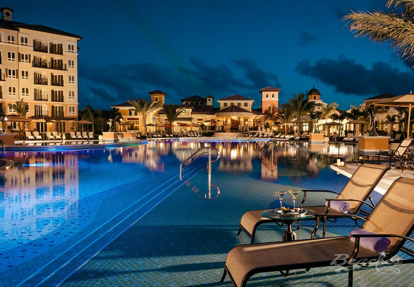 lounge chairs on a pool in front of a luxury resort, luxury all inclusive vacation packages