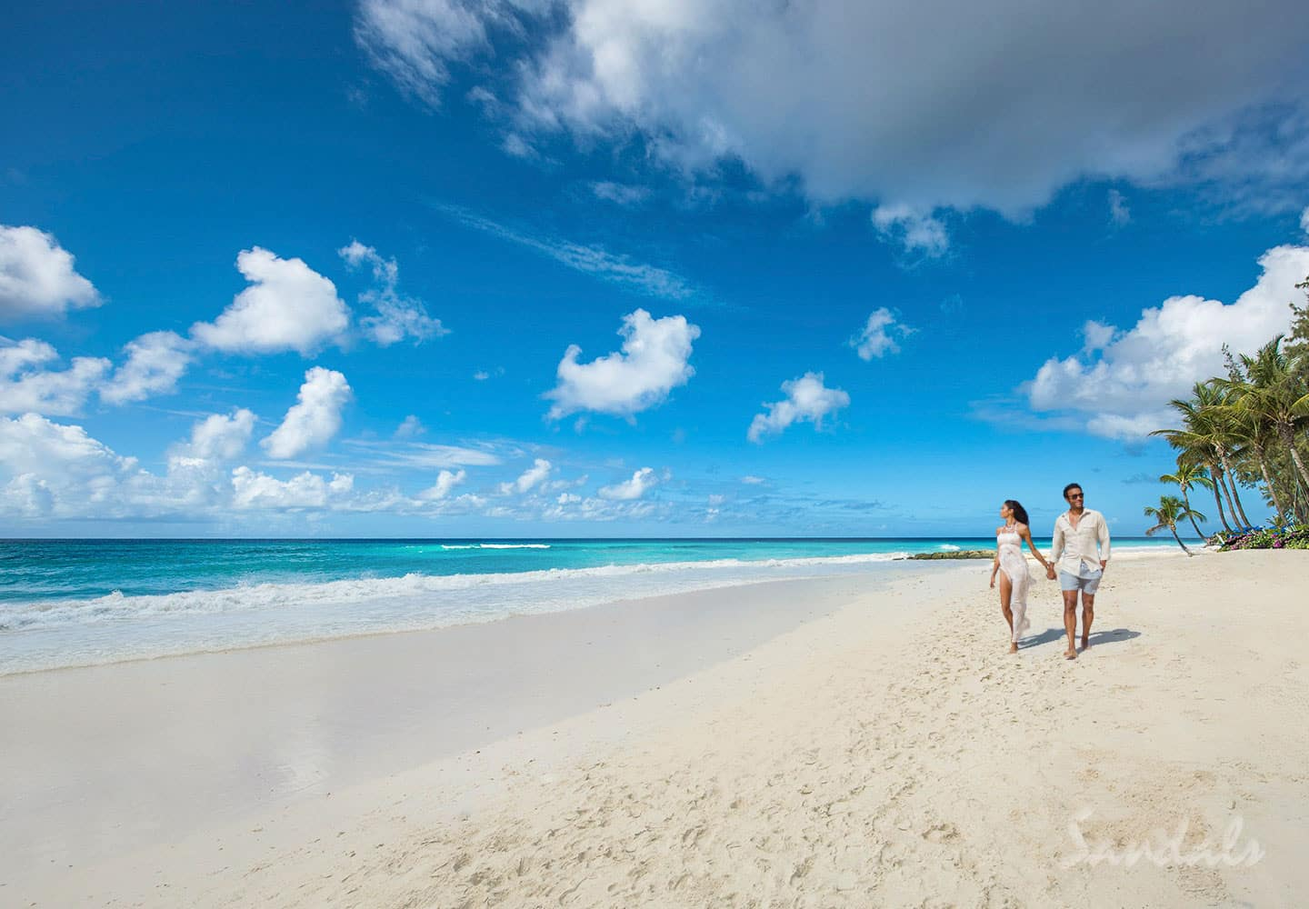 couple walking on the beach, enjoying their honeymoon at the Sandals Barbados resort, adult only vacations can be booked with Southern Travel Agency Augusta, GA