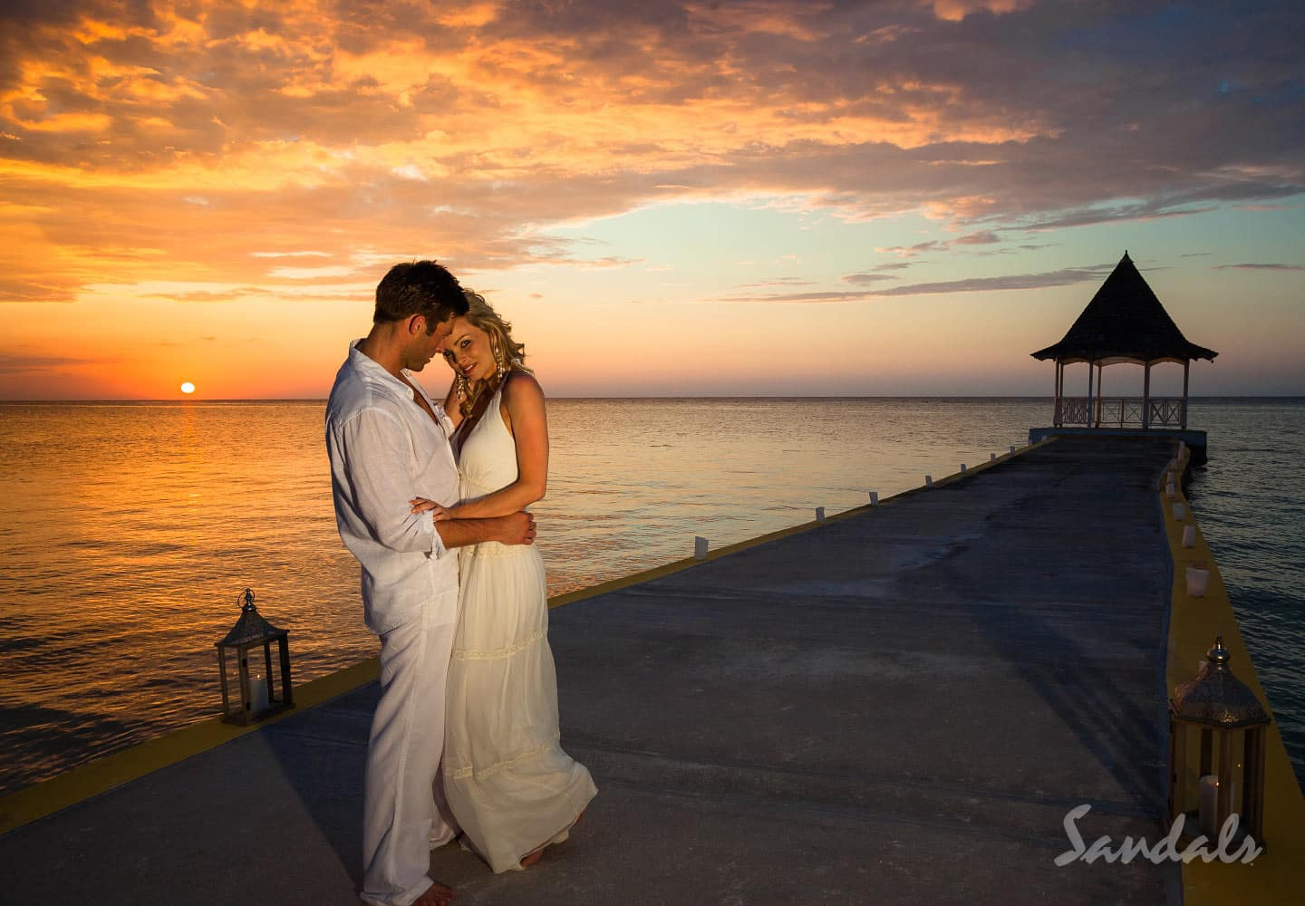 couple standing on a pier at sunset at the Sandals Montego Bay resort in Jamaica, perfect location for luxury all inclusive vacation packages, booked by Southern Travel Agency Augusta, GA