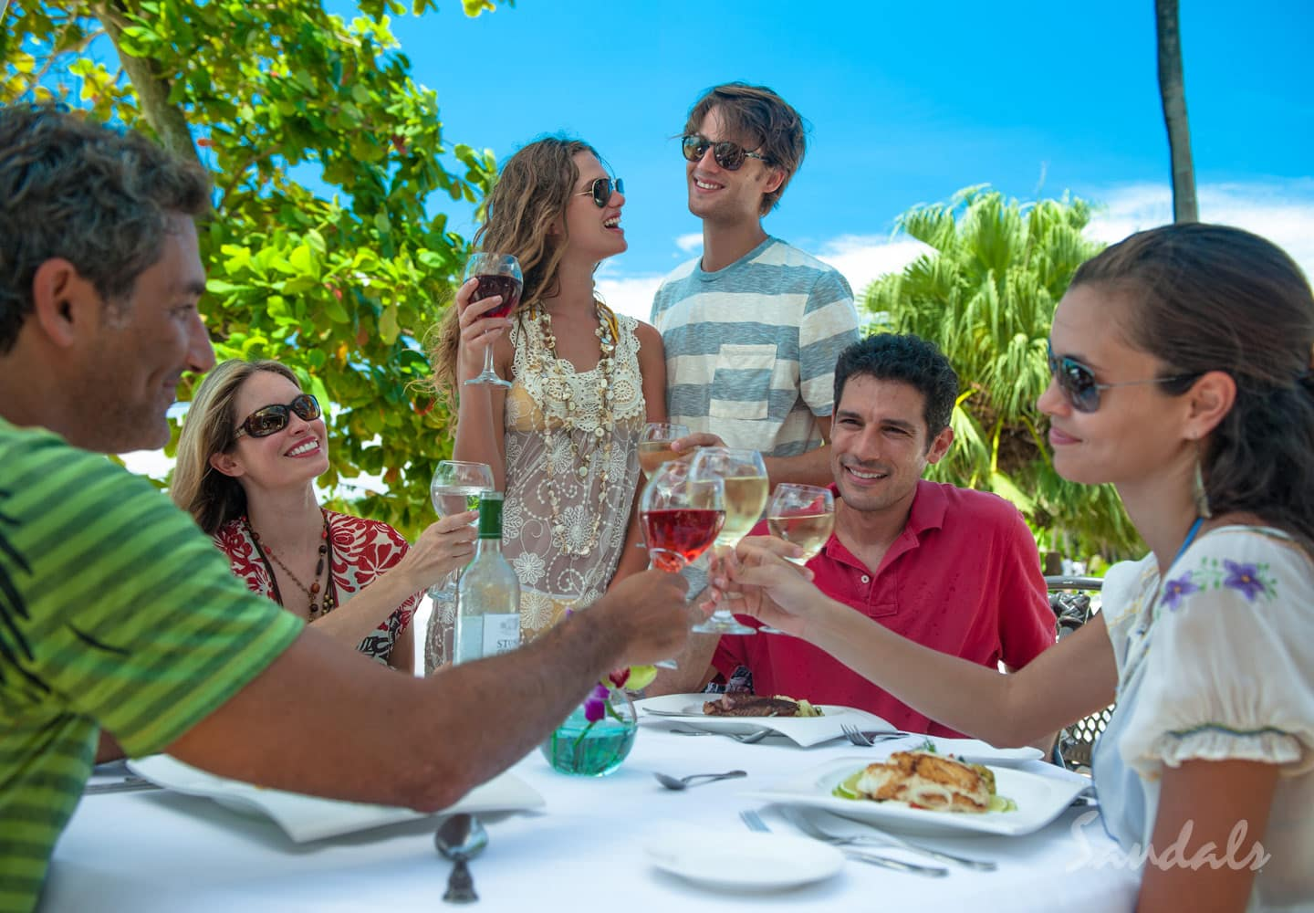 a group of people enjoying the outsides, eating and drinking at the luxury Sandals Negril Beach resort in Jamaica, perfect location for luxury all inclusive group vacations, planned by Southern Travel Agency Augusta, GA