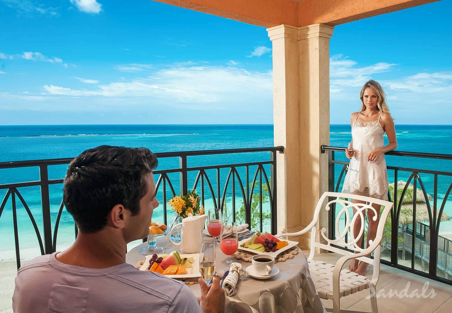 couple on their private balcony with ocean view at the Sandals all inclusive vacation resort South Coast Whitehouse, Jamaica