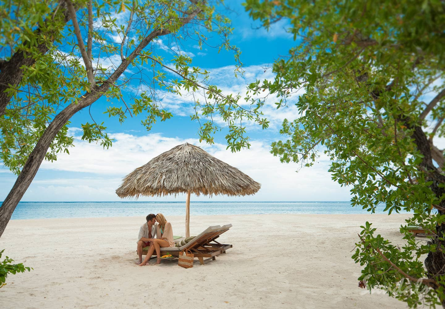 couple in their romantic spot on the beach at Sandals Whitehouse, now Sandals South Coast in Jamaica, honeymoons and all inclusive vacations adults only can be booked with Southern Travel Agency Augusta, GA