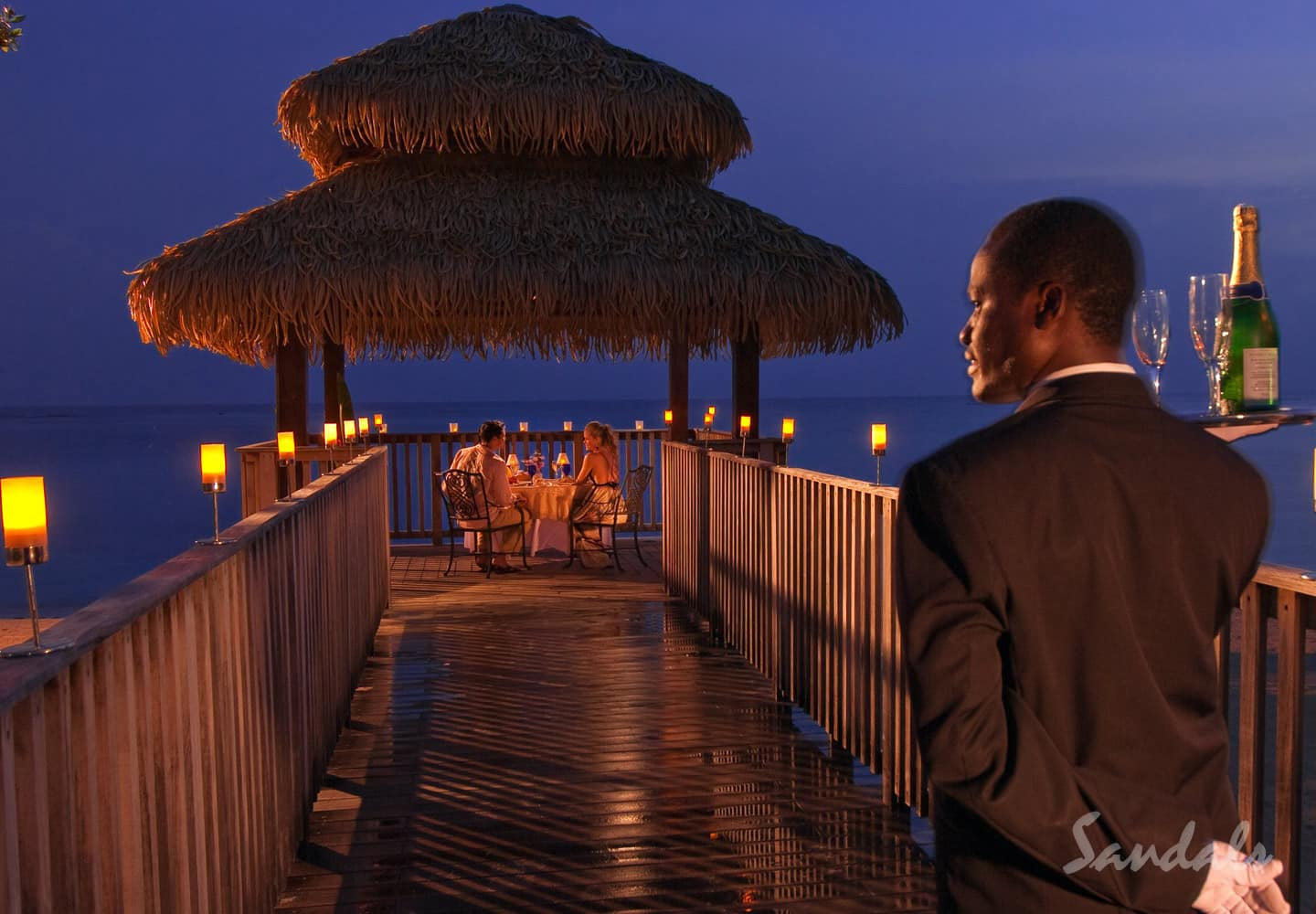 couple on their private candlelight dinner at the end of pier, butler waiting with meals and drinks at the beginning of the pier at Sandals South Coast in Whitehouse, Jamaica, honeymoons and all inclusive vacations adults only can be booked with Southern Travel Agency Augusta, GA
