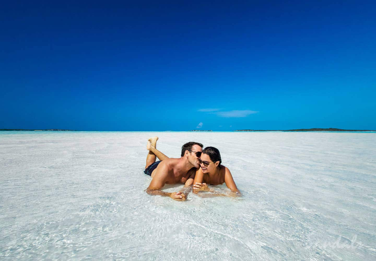 couple laying in the sand in the ocean, all inclusive adults only vacation packages at Sandals Emerald Bay golf, spa and tennis resort at Great Exuma, Bahamas, Southern Travel Agency Augusta, GA