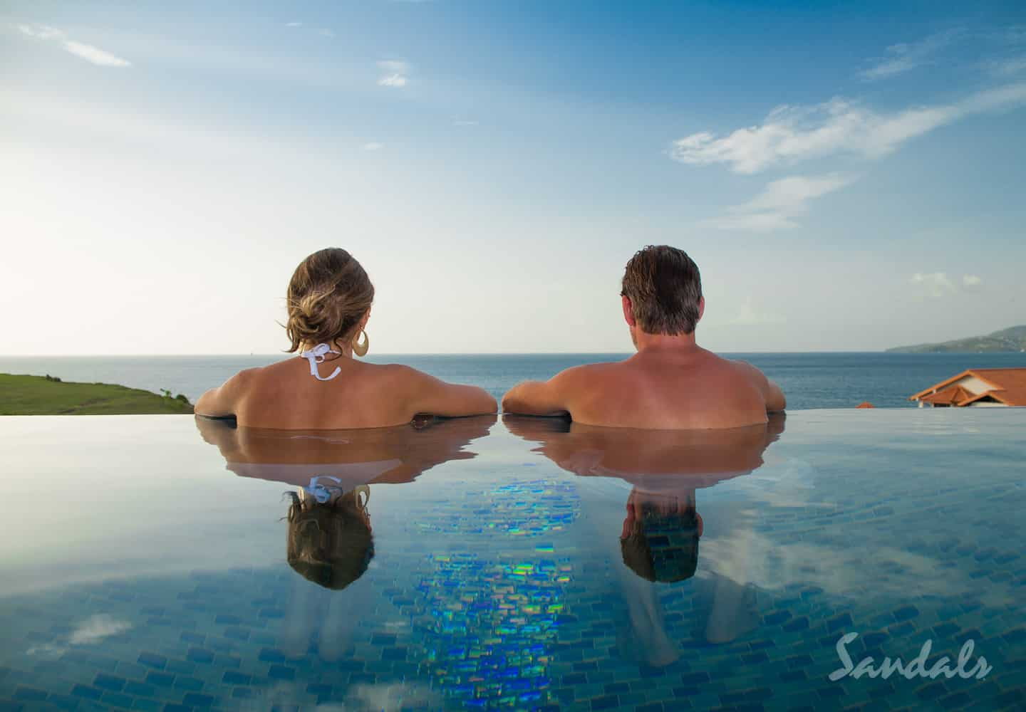 a couple in their private plunge pool overlooking the resort and the ocean at Sandals LaSource Grenada, an all inclusive luxury resort for adults only, Southern Travel Agency Augusta, GA