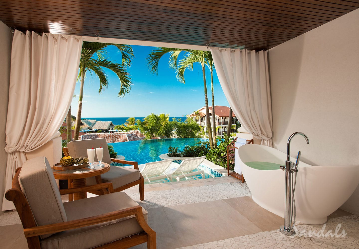 luxurious resort room with champagne on the table, deluxe bathtub and private plunge pool at Sandals LaSource Grenada, luxury resort for adults only, Southern Travel Agency Augusta, GA