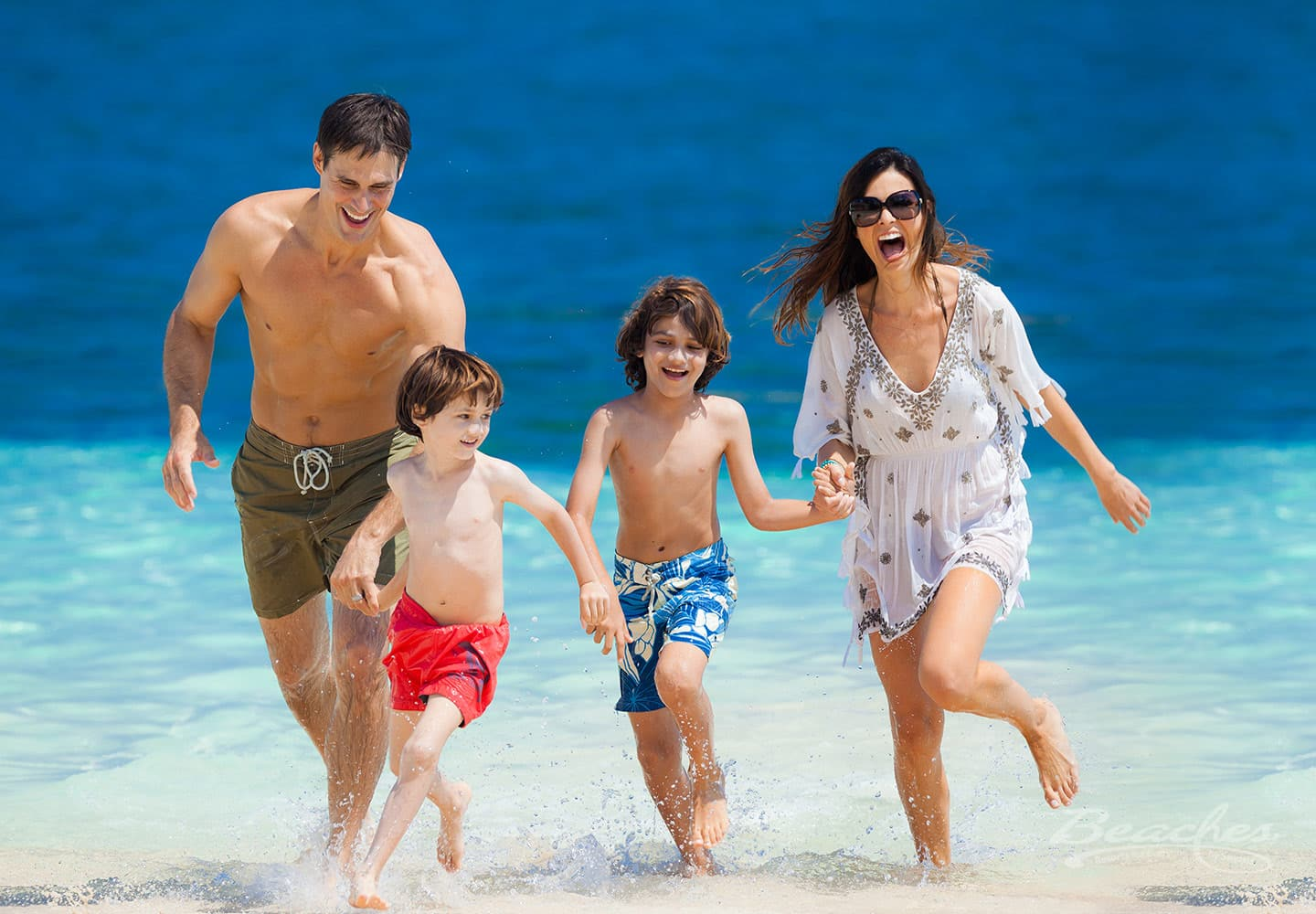 family walking on the beach, holding hands, laughing and having a good time at the Beaches Ocho Rios family resort in Jamaica, trip can be booked with online travel agency Southern Travel Agency Augusta, GA