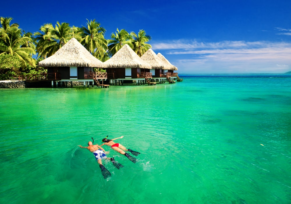 a couple scuba diving in front of over-the-water bungalows in clear blue-green water on their tahiti honeymoon vacation