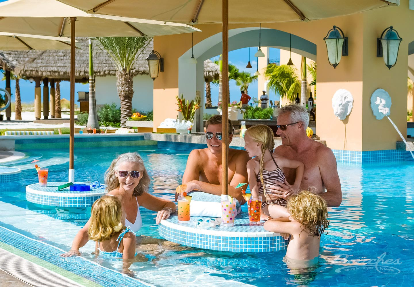 family in a waiting pool at the luxury all inclusive beaches turks and caicos resort during their family vacations