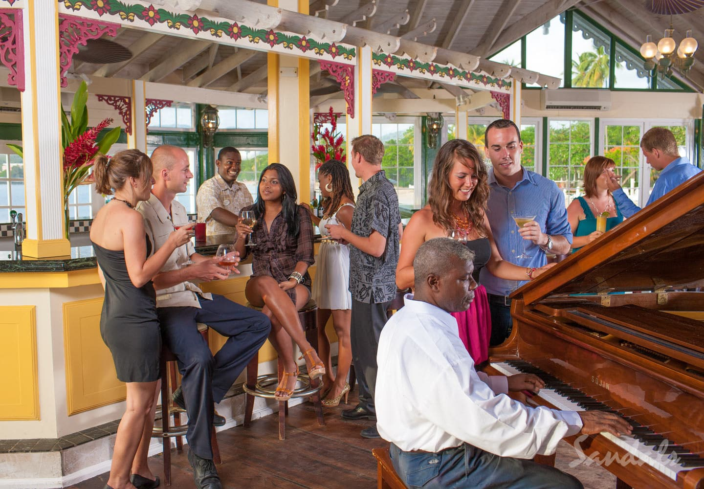 woman and men having a good time, listening to music and chatting at the bar at the sandals hylcyon beach resort in st. lucia during their all inclusive group vacations