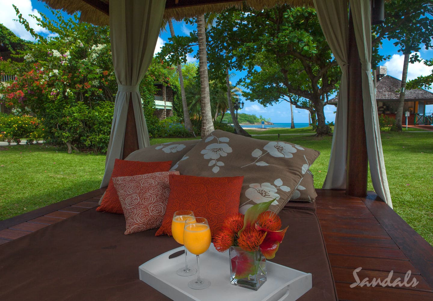 garden lounger with a bouquet of flowers, pillows and two cocktail glasses at the Sandals Halcyon beach resort in St Lucia, trip can be booked with online travel agency Southern Travel Agency Augusta, GA