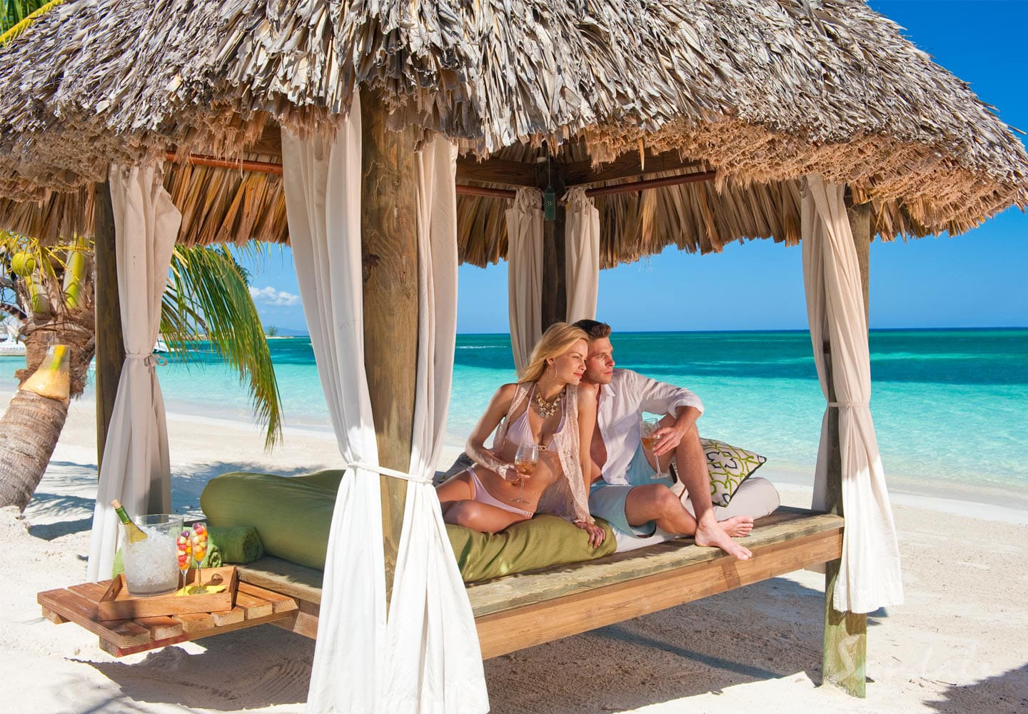 couple on a beach lounger at Sandals Montego Bay in Jamaica, resort can be booked with online travel agency Southern Travel Agency Augusta, GA