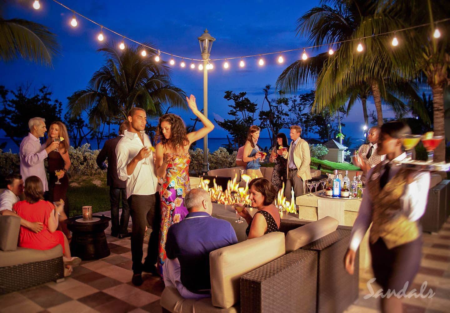 people dancing, drinking, and having a good time, entertainment at Sandals Whitehouse, now South Coast, in Jamaica, vacation can be booked with Southern Travel Agency Augusta, GA