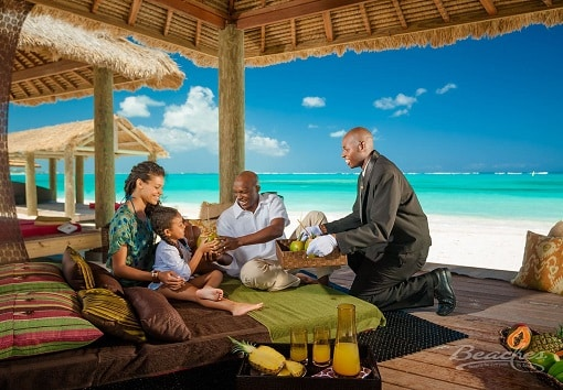butler serving family at their beach lounger at Beaches Turks and Caicos family resort, trip can be planned by Southern Travel Agency Augusta, GA