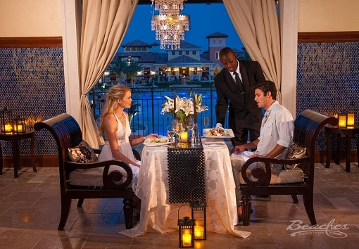 couple dining in a private room and having a romantic dinner at the Beaches Turks and Caicos resort, family vacation can be planned by Southern Travel Agency Augusta, GA