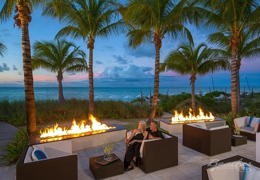 couple sitting on a fire pit on the beach at sunset at the Beaches Turks and Caicos family resort, family vacation can be planned by Southern Travel Agency Augusta, GA