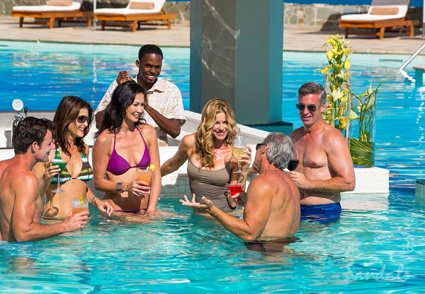 men and women in their bathing suits with butler in pool bar, enjoying the sunshine on their luxury all inclusive vacation packages adult only trip.