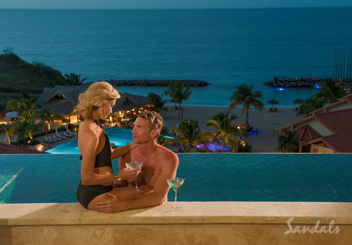 a couple in pool, drinking cocktails and having fun, overseeing a Sandals resort, symbolizing the beauty and joy of booking all inclusive vacations adults only trips