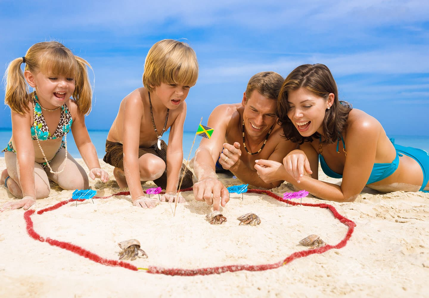 family on the beach, playing in the sand at the Beaches Negril family resort, family vacation packages can be booked through Southern Travel Agency Augusta, GA