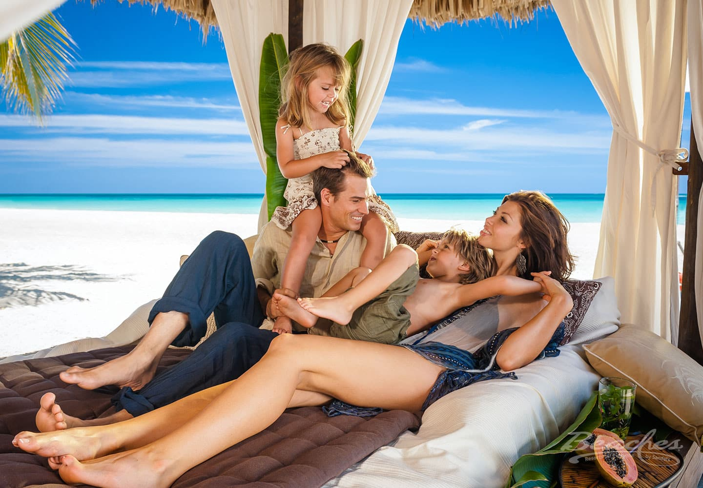 father, mother, daughter, and son on a bed on the beach on their Beaches Negril luxury all inclusive family vacations trip