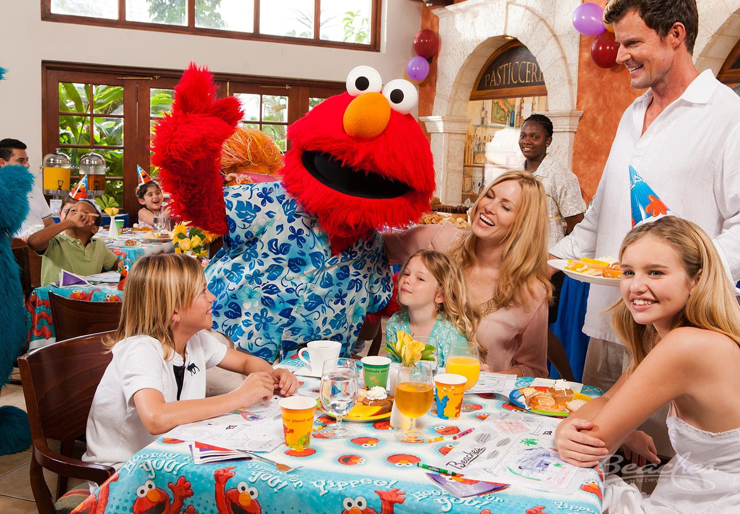 a family, mother, father, and three children, at the breakfast table, visited by one of the Sesame Street characters at the Beaches Ocho Rios family resort in Jamaica, all inclusive family vacation packages offered by Southern Travel Agency Augusta, GA