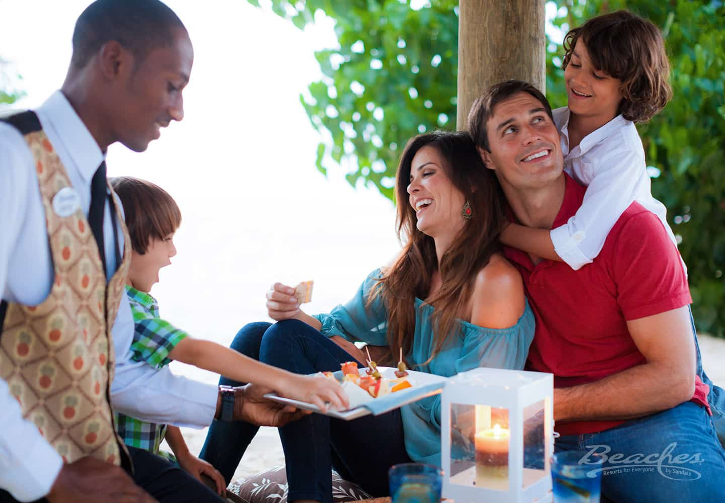 mother, father, and two kids laughing and having a good time, a butler is serving them appetizers at the Beaches Ocho Rios family resort in Jamaica, family vacation packages offered by Southern Travel Agency Augusta, GA