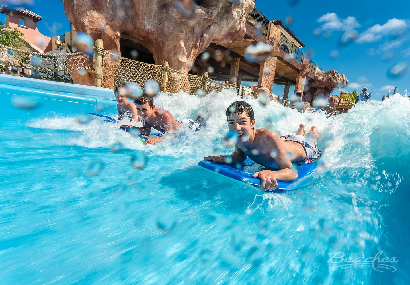 boys racing to be first with their surf boards in one of the waterparks at Beaches Turks and Caicos, family vacation packages can be booked through Southern Travel Agency Augusta, GA
