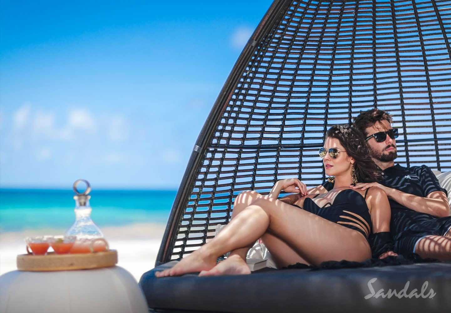 couple sitting in a wicker swing at the Sandals Barbados resort, well-known for its all inclusive vacations adult only