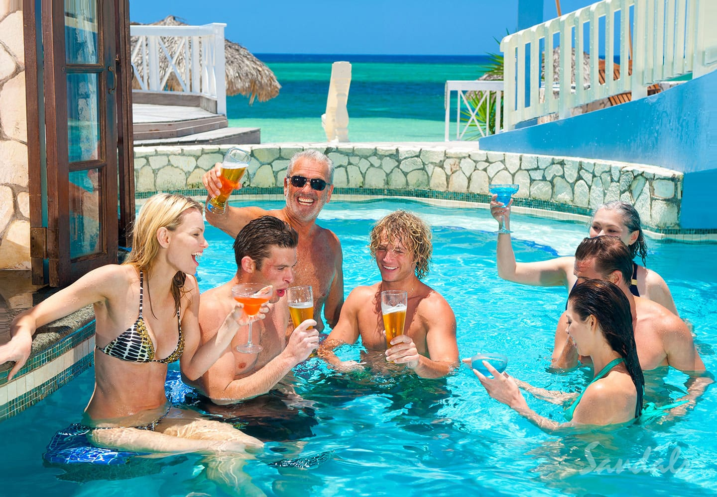 a group having fun and partying in a pool bar at Sandals Montego Bay, all inclusive group vacation packages