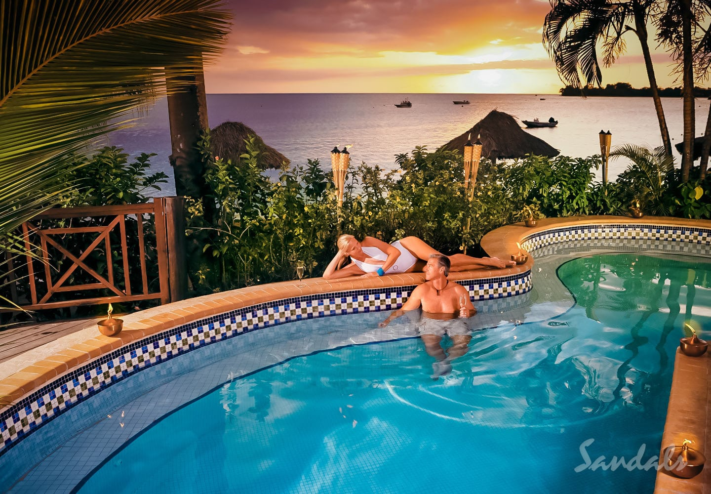couple in their private pool at sunset, ocean and resort in the back at the Sandals Negril beach resort in Jamaica, perfect location for all inclusive vacations adults only, planned by Southern Travel Agency Augusta, GA