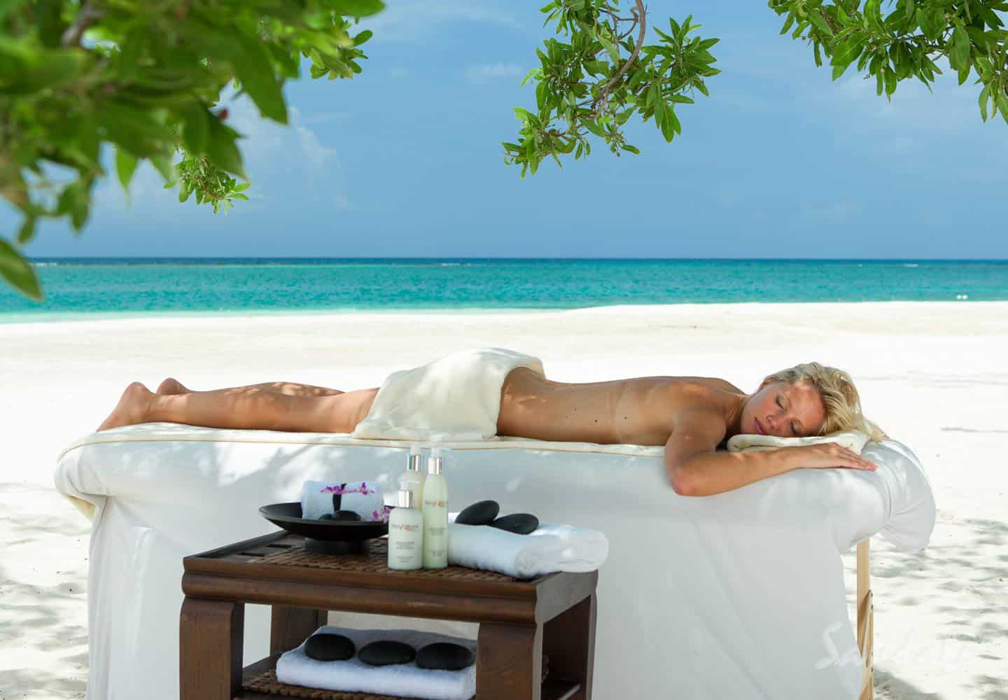 woman laying on a massage table on the beach, cold beverage are on a serving table close by at Sandals South Coast Whitehouse Jamaica resort, perfect location to relax and for all inclusive vacations adults only, planned by Southern Travel Agency Augusta, GA
