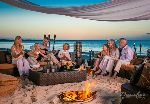 group of people sitting together around the fire pit, singing, laughing and having a good time, available as all inclusive group vacations, planned by Southern Travel Agency Augusta, GA