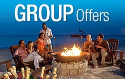 happy people around a campfire on the outside porch, promoting all inclusive Sandals group vacations