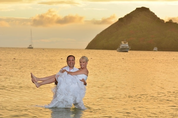 Groom and bride staying in the ocean, groom holds the bride in white wedding dress at Sandals La Grande St Lucia beach and spa resort