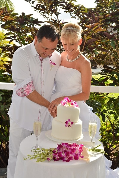 bride and groom cutting the wedding cake at the Sandals La Grande St Lucia beach and spa resort