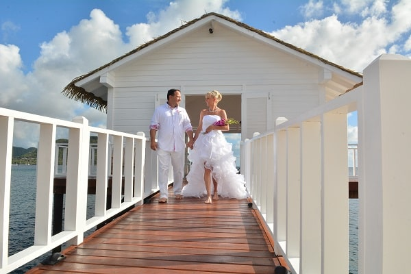 bride and groom walking over the pier, behind them the over-the-water bungalows at Sandals La Grande St Lucia beach and spa resort
